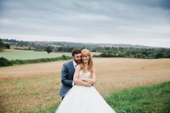 Bride and Groom Cuddle with country views behind Claverdon church hall wedding