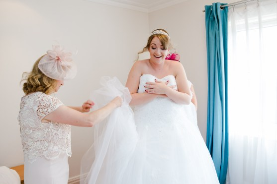 bride getting into dress helped by two mothers