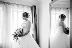 bride poses next to window with mirror reflecting from behind