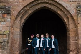 groom and groomsmen pose under archway of coach house