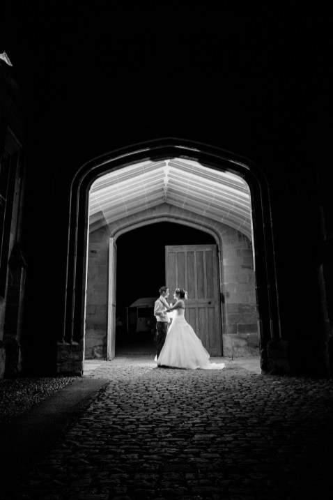 Night time shot of bride and groom in archway Stoneleigh Abbey Wedding Photography