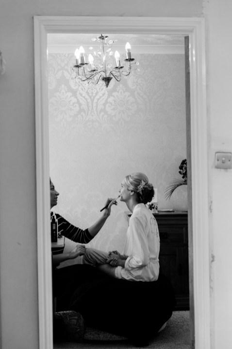 Bride having her makeup done at home framed in doorway