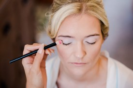 bride having her makeup done on her wedding morning from high angle