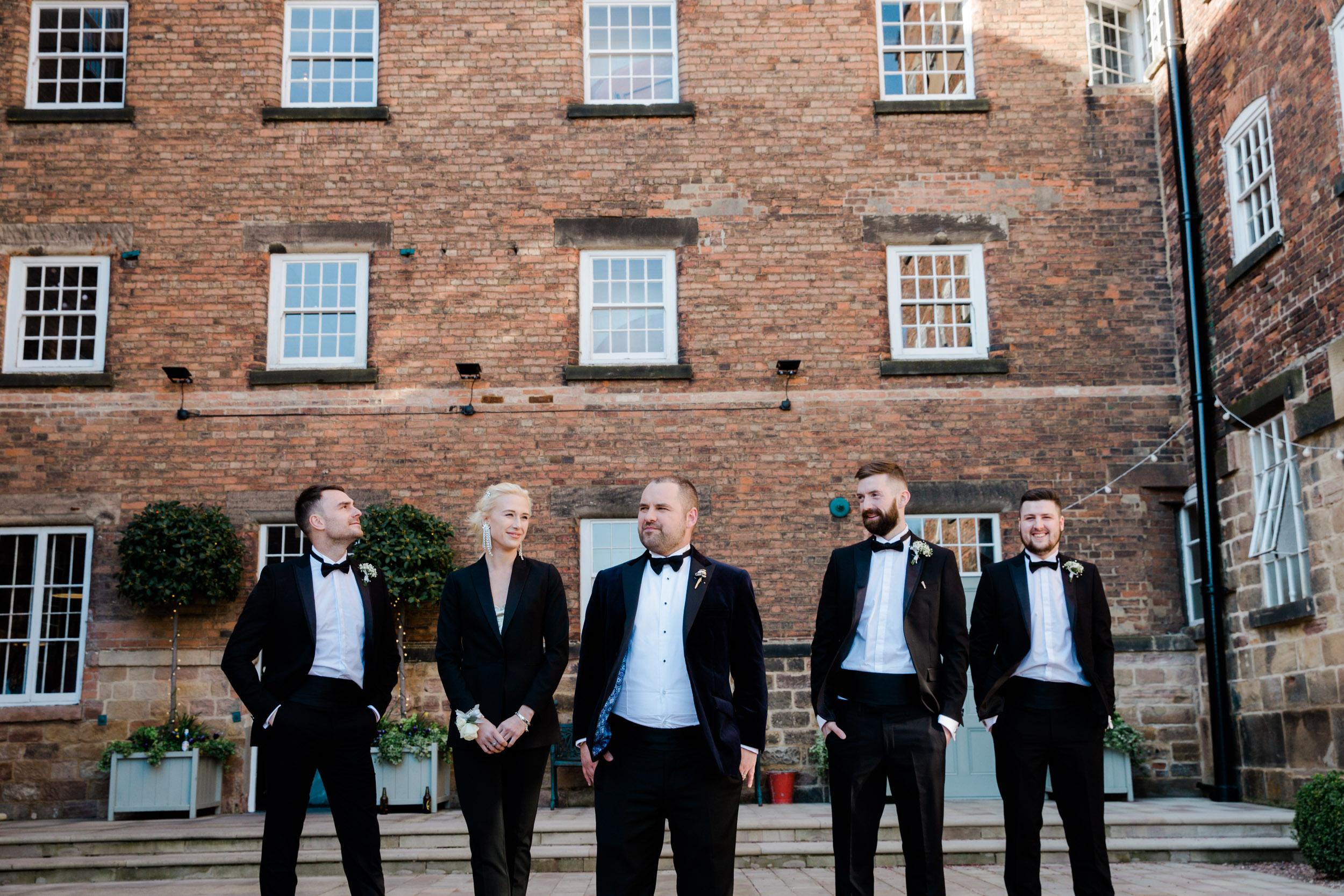 groom and groomsmen wearing tuxedo outside west mill