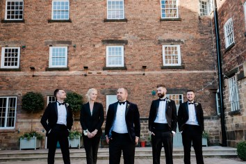 groom and groomsmen wearing tuxedo outside west mill