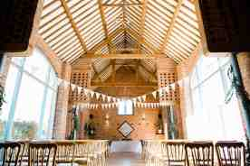 wedding ceremony room at swallows nest barn with bunting detail