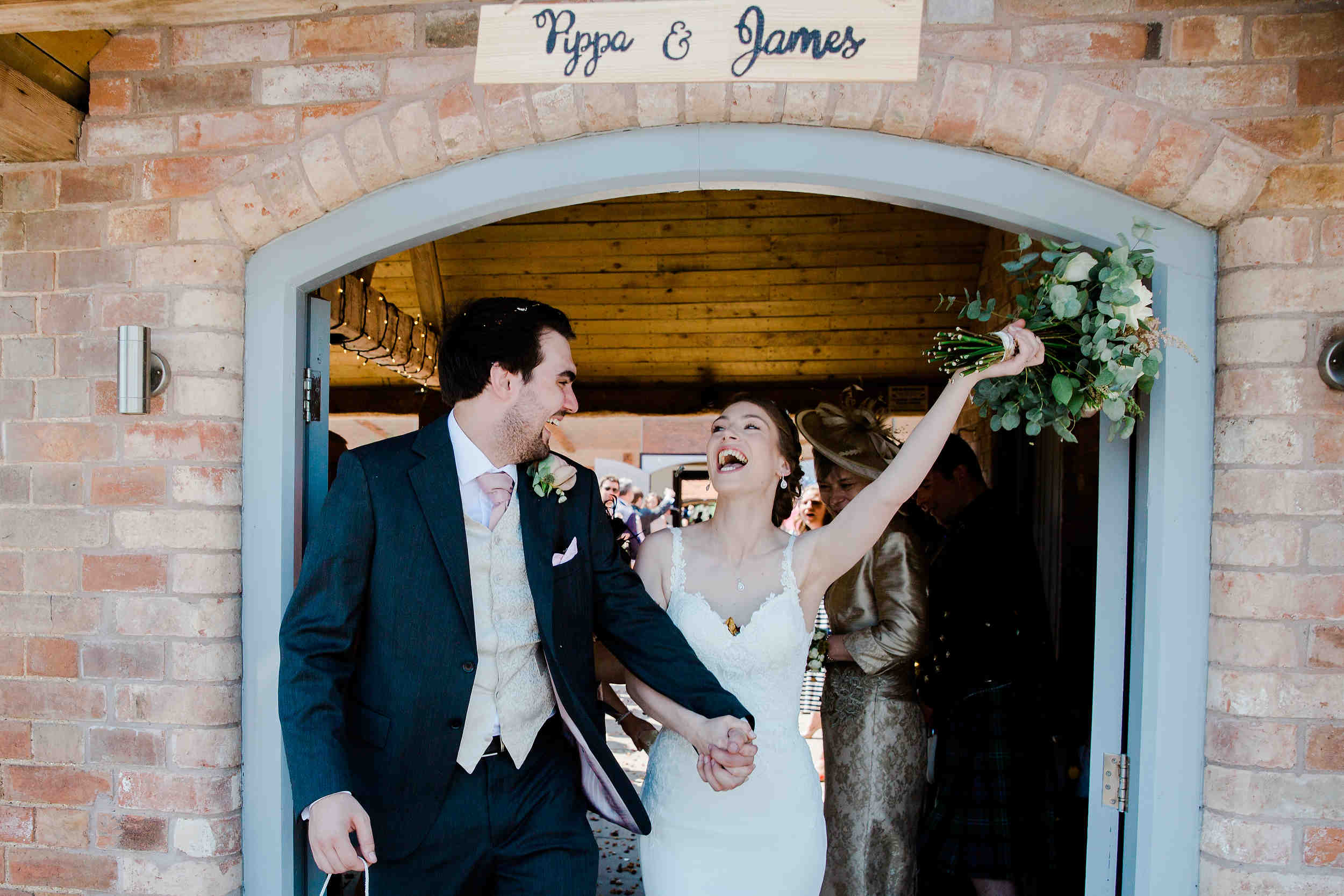 bride and groom celebrate walking through the tunnel of confetti at swallows nest barn