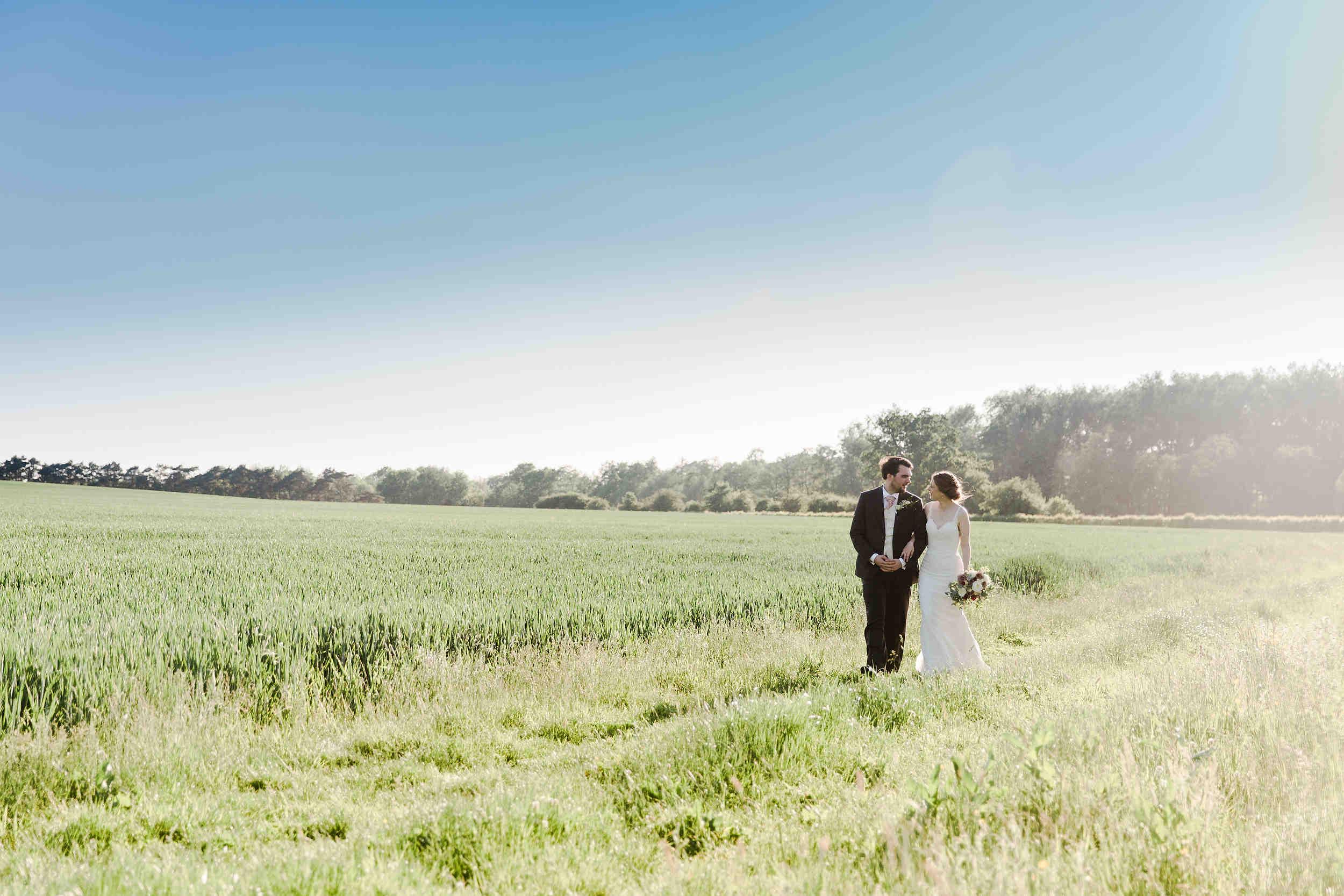 couple walk through feilds at swallows nest barn