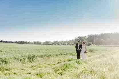 couple walk through feilds at swallows nest barn
