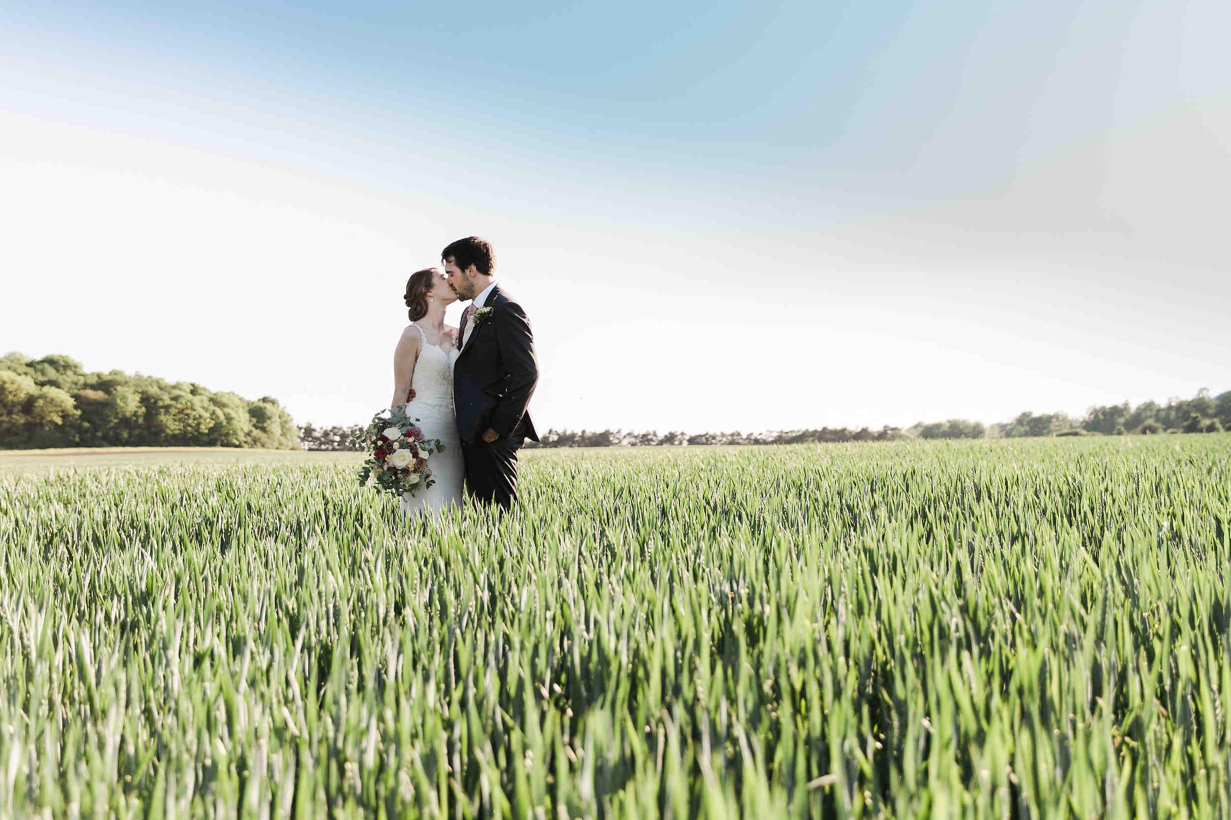 couple kiss in field swallows nest barn
