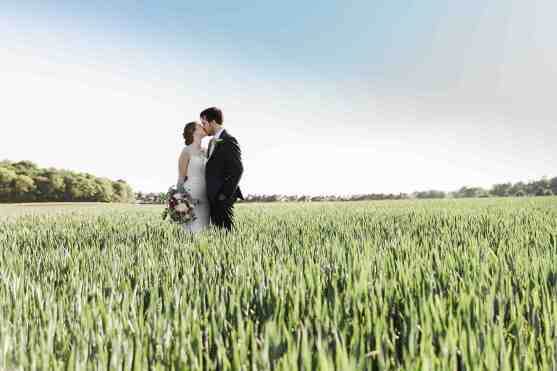couple kiss in field swallows nest barn
