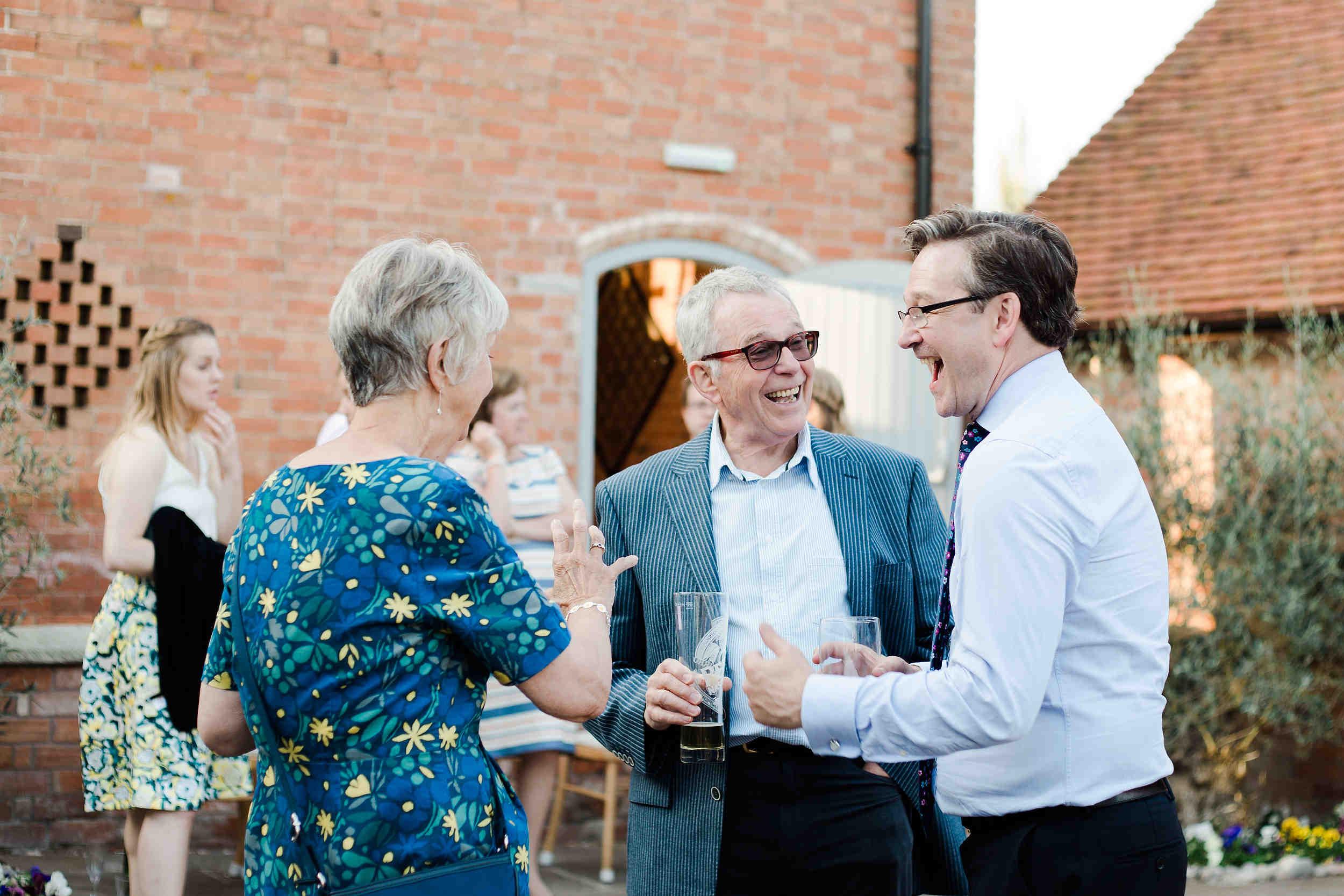 candid photos of guests laughing barn wedding warwick stratford