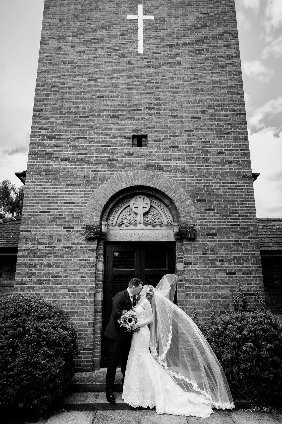 bride and groom kiss outside church sutton coldfeild