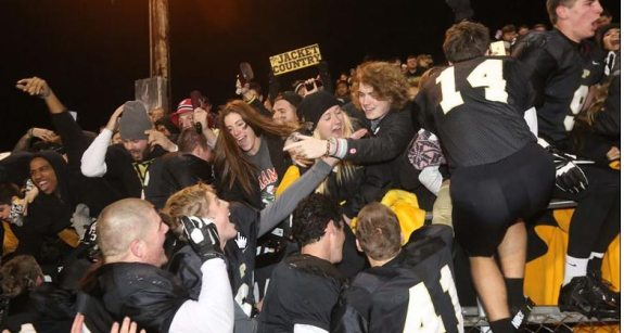 Perrysburg's football team celebrates with tudents after the 56-7 rout. THE BLADE/KATIE RAUSCH