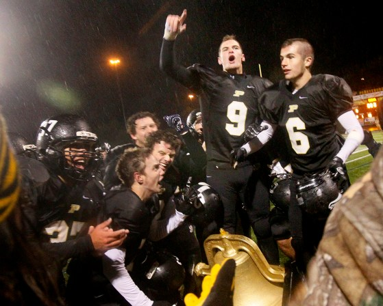 Perrysburg's senior Jack Barteck (9), Scott Freeman (6) and their teammates cheer after the Maumee victory.