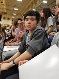 Eighth grader sitting in the stands of Froshfest