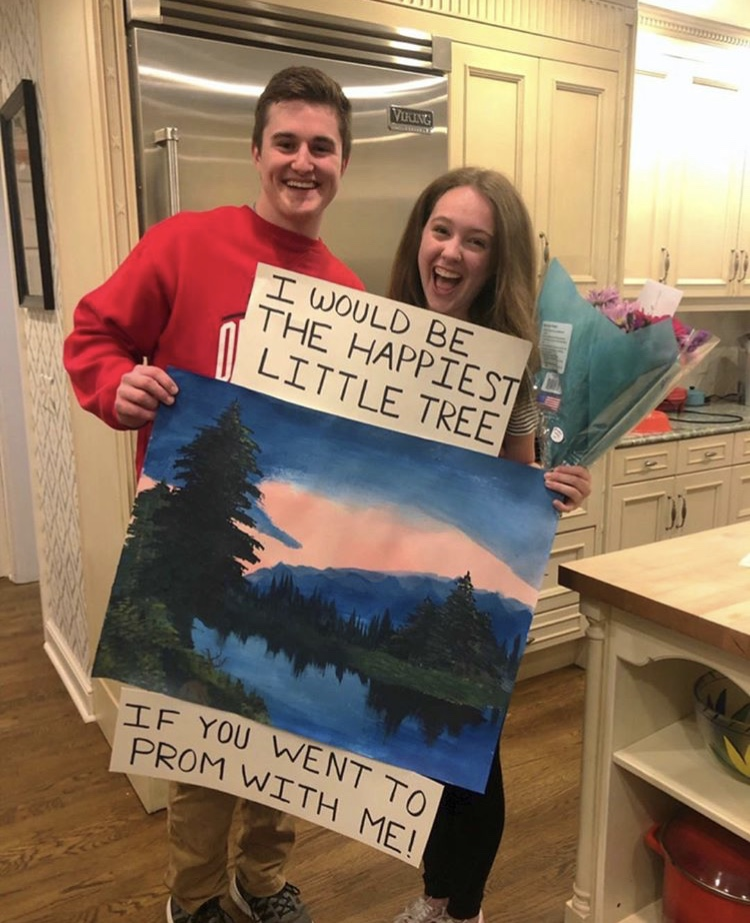 """A sign that says """"I would be the happiest little tree if you would go to prom with me"""" above a Bob Ross painting"""