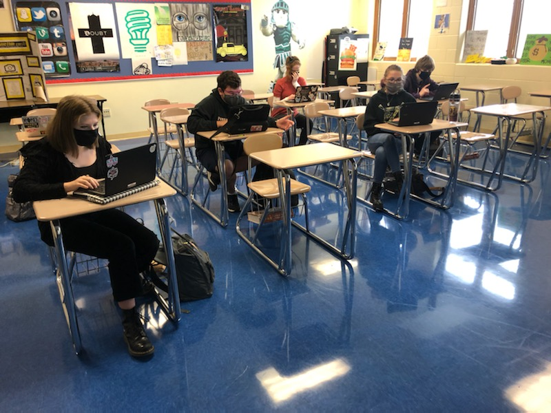 students sitting socially distanced in masks in a class room