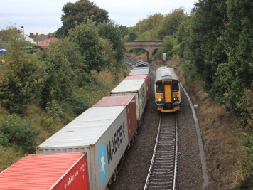 derby_road_-_greater_anglia_153335_passing_freightliner_66538_and_container_train