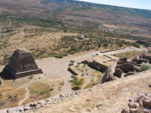 Vista de la pirámide votiva, y a la derecha, el juego de pelota con la clásica forma de i latina.