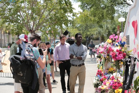 E:60 correspondent Bob Woodruff stands behind Chris Singleton as they observe a memorial to the shooting victims. (E:60)