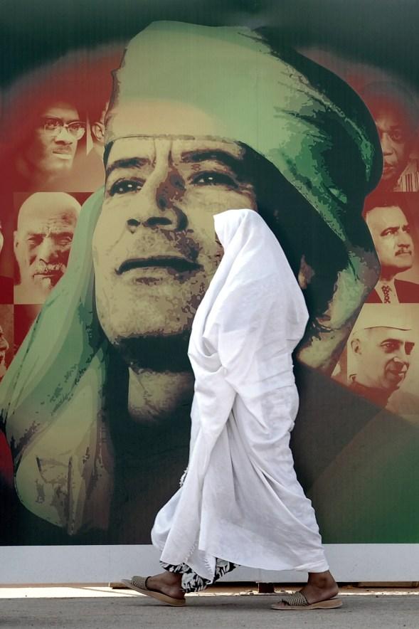 """Ammar Abd Rabbo A woman passes a giant poster of Libyan leader Muammar Gaddafi in Tripoli, a day before the 40th anniversary of the """"Al Fateh"""" revolution, 30 agosto 2009 Stampa fine art su carta di cotone 91 x 61 cm © Ammar Abd Rabbo Courtesy of Ayyam Gallery, Dubai"""