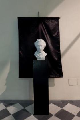 """Black Flag, Unfinished Marble (Gino Lucetti) Marmo di Carrara scolpito da """"Telara Studio d'Arte"""" da Adriano Gerbi, Mauro Tonazzini, Sara Atzeni (assistente), Maria Teresa Telara (direttrice di produzione), bandiera di raso, tubo in acciaio; dimensione variabile (busto, 45 cm x 28 cm x 20 cm); 2011. Courtesy Franco Soffiantino Contemporary Art Productions, Torino"""