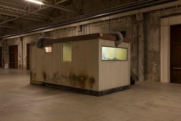 Micol Assaël, Mindfall, 2004-07, installazione, cabina con vetri appannati (container), motori elettrici, cavi elettrici, fumo, tavoli, sedia Mixed media, 252x557x250 cm Foto Agostino Osio Courtesy Micol Assaël e Johann König, Berlin