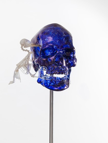 Jan Fabre, Skull with Woodpecker, 2017, Murano glass, skeleton of a woodpecker, Bic ink, stainless steel, 53.6x24.9x22.3 cm Photographer Pat Verbruggen Copyright Angelos bvba
