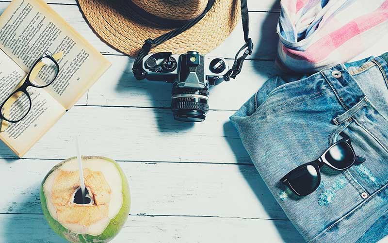 A Seguros Promo é confiável? Na foto, há Itens de viagem como câmera fotográfica e óculos de sol (Foto: Pixabay)