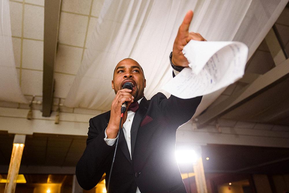 Photojournalistic wedding photo of groomsman giving speech