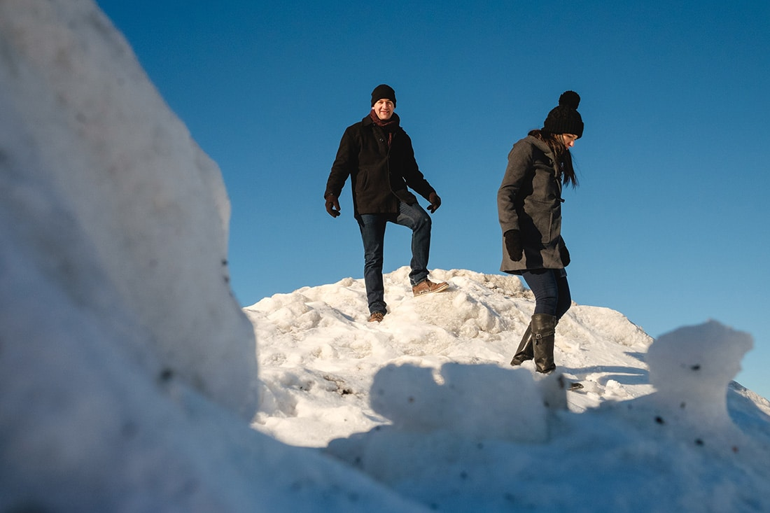 Engaged couple climbing mountain of snow in winter engagement photos