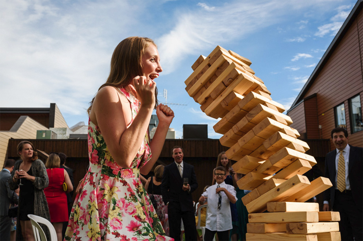 Award-winning wedding photo of jenga block tower falling on wedding guest
