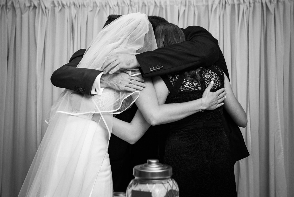 Emotional wedding ceremony with family hugging at Hotel Nelligan