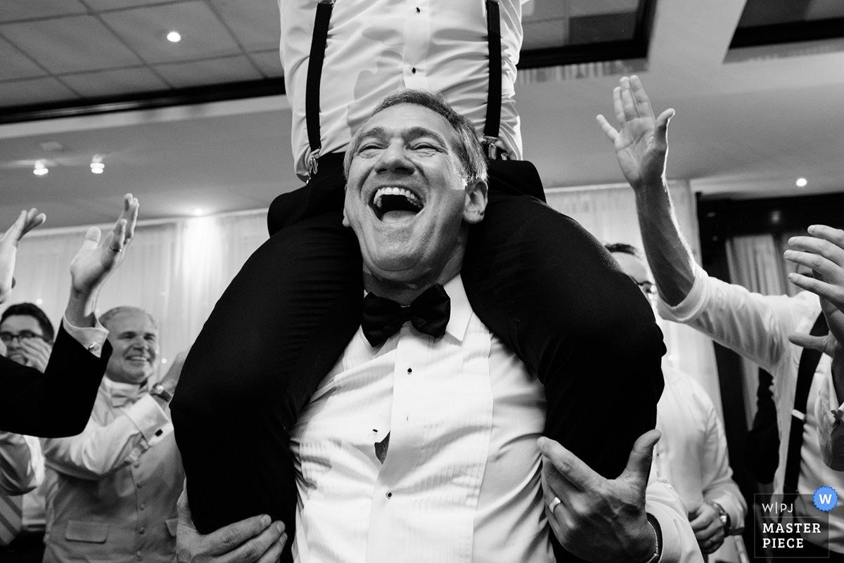 Award-winning wedding photo of father lifting the groom