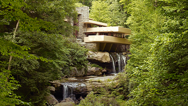 The Fallingwater house, tucked behind trees with a waterfall coming out of the side.