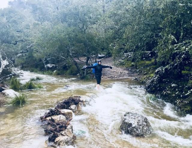Wanderer balanciert auf überfluteter Steinbrücke auf dem GR 221