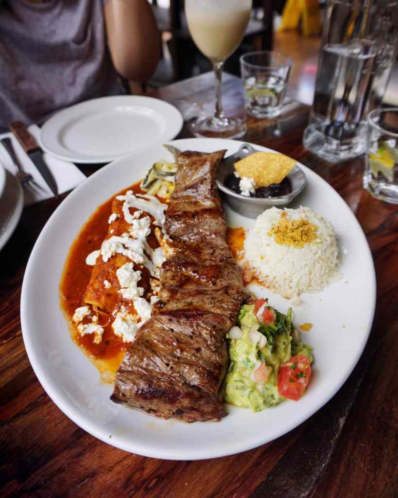Image of a plate of grilled beef fillet with rice, guacamole, enchilada and beans at Mestizo Restaurant