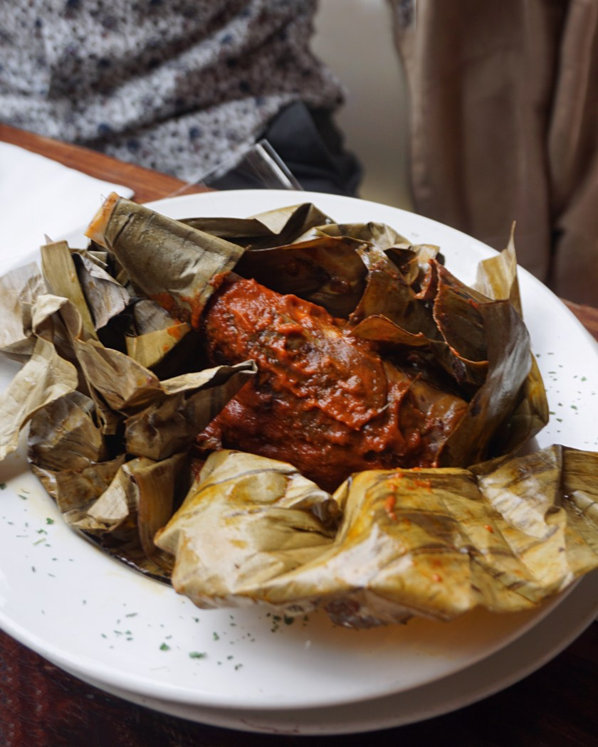 Image of a plate of Lamb Shank wrapped in banana leaves at Mestizo Restaurant