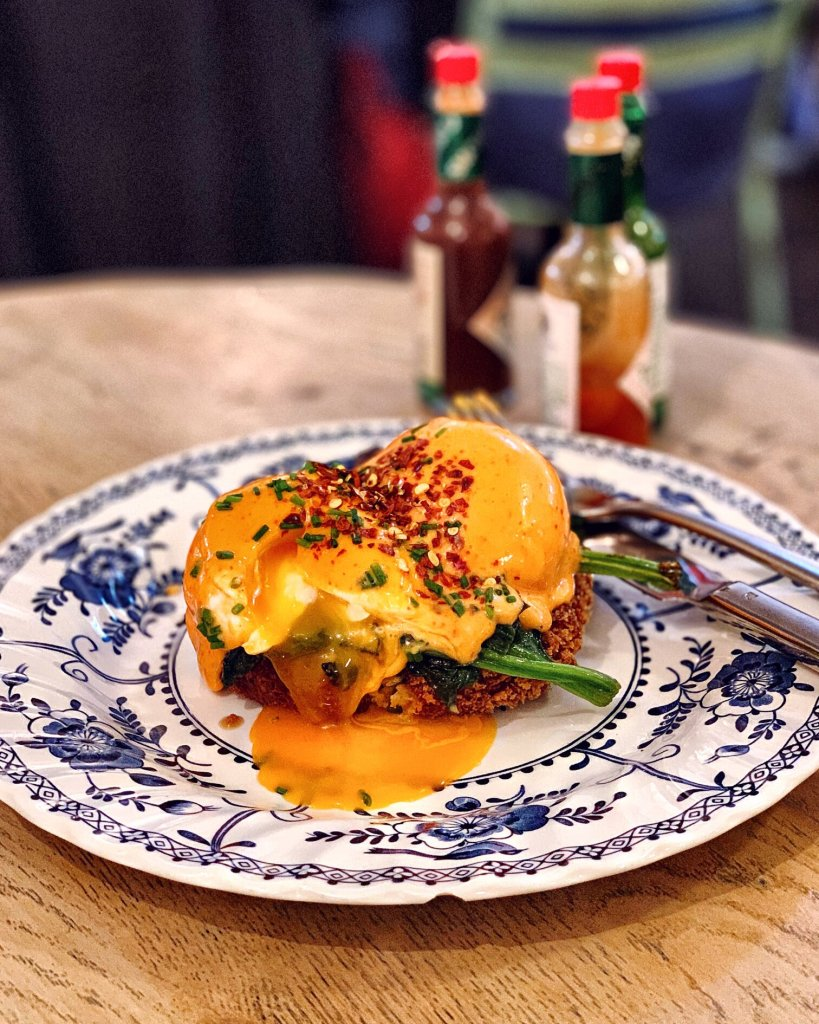 Crab Cake topped with Spinach, Poached Egg, and Sriracha Hollandaise at Eggbreak Nottinghill, London