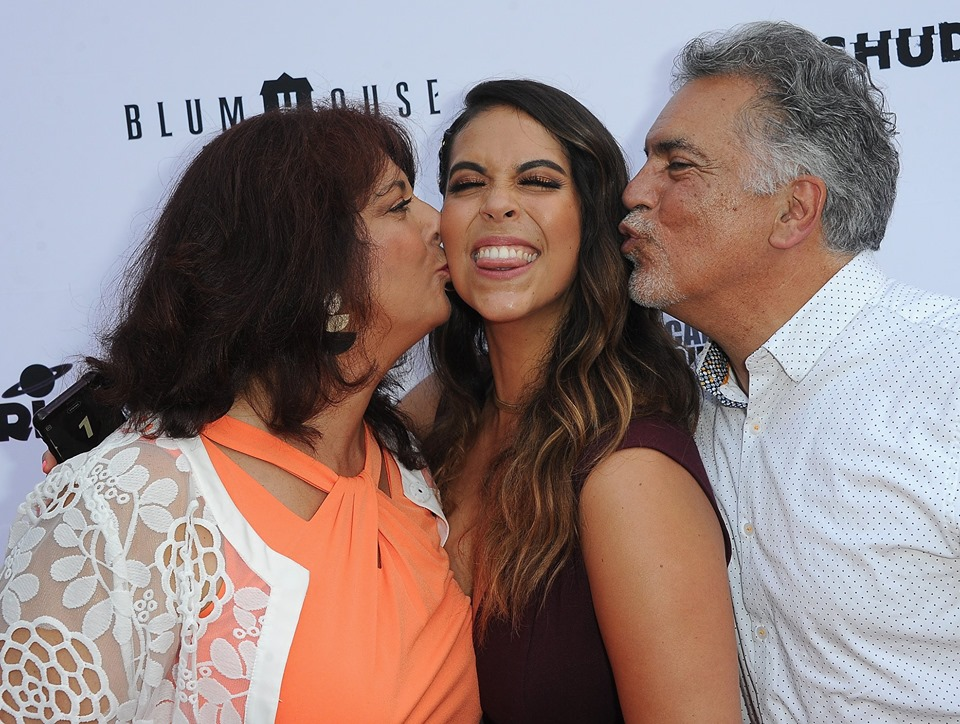 "Gigi Saul Guerrero being kissed by her parents, Fabiana and Raul Saul, on the red carpet at Etheria 2019 for her screening of ""Culture Shock"""