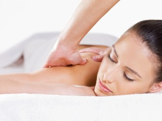Close-up portait of relaxing woman having massage on her shoulder - white background