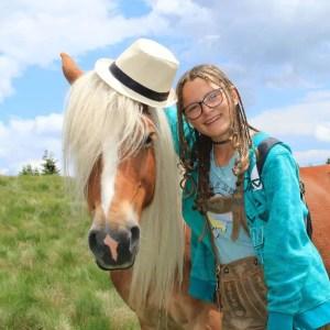 cavallo haflinger con cappello di paglia ragazza in pantaloni di pelle tirolesi