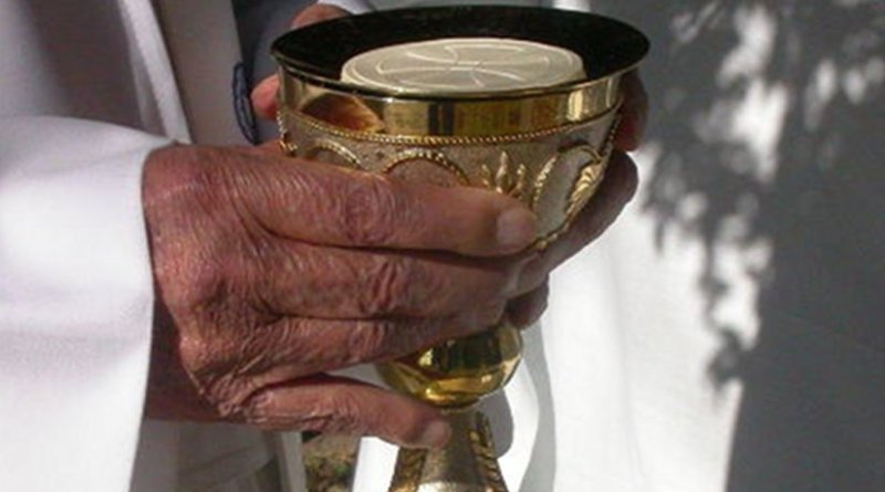 Priest preparing Holy Communion.