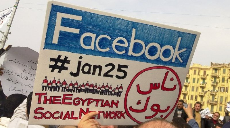 """A man during the 2011 Egyptian protests carrying a card saying """"Facebook,#jan25, The Egyptian Social Network"""". Photo by Essam Sharaf, Wikipedia Commons."""