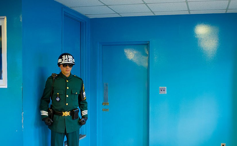 An ROK soldier protects the door to North Korea in the building where the armistice was signed between North and South Korea. Photo by Severin Stalder, Wikipedia Commons.