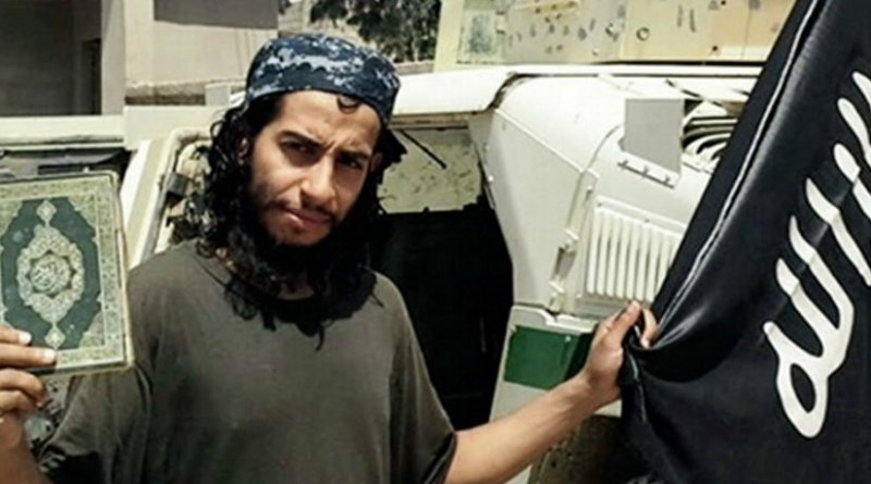 Abdelhamid Abaaoud holding the Quran and a black flag of the Islamic State. Photo Credit: Islamic State propaganda.