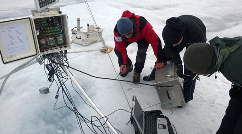 Researchers service one of PROMICE's automatic weather stations on the Greenland ice sheet that was used in the study. Credit Photo by William Colgan, York University