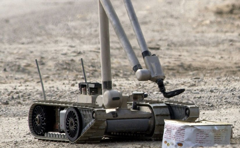 """A U.S. Army explosive ordnance disposal (EOD) robot, """"i-Robot"""", pulls the wire of an alleged improvised explosive device (IED), found by the Iraqi Police. U.S. Navy photo by Journalist 1st Class Jeremy L. Wood, Wikipedia Commons."""