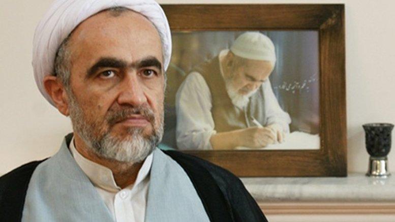Ahmad Montazeri sits in front of a portrait picture of his late father Hossein Ali Montazeri. Photo via Radio Zamaneh.